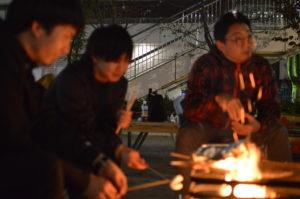 焚き火を囲む男性