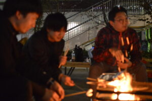 焚き火台を囲む男性